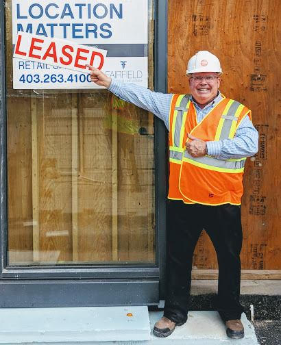 "Michael Kehoe next to a ""Leased"" sign for Hart Healthy Foods in the summer of 2018"